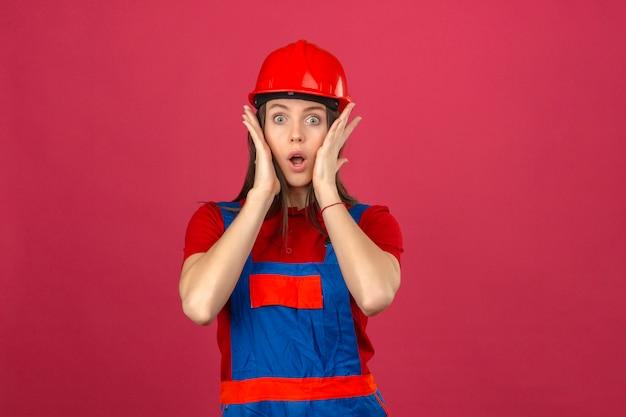 暗いピンクの背景にカメラを見て彼女の顔に触れるショックを受けた建設の制服と赤い安全ヘルメットの若い女性