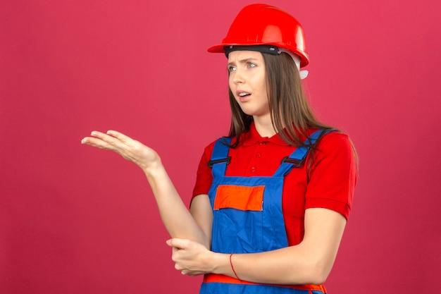 濃いピンクの背景に彼女の不快感を示す建設の制服と赤い安全ヘルメットの若い女性