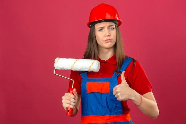 Молодая женщина в строительной форме и красный защитный шлем, показывая знак ок с скептическим выражением держит валик на темно-розовом фоне