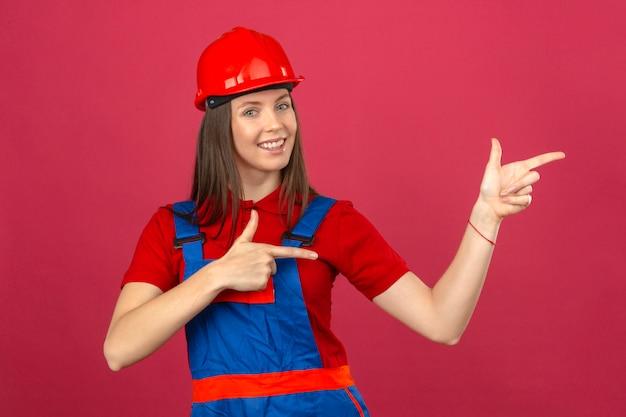 カメラを見て笑みを浮かべて、濃いピンクの背景に立っている側に手と指で指している建設の制服と赤い安全ヘルメットの若い女性
