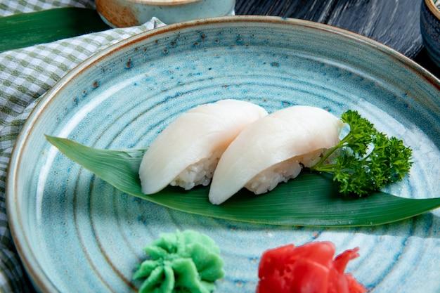 Вид сбоку суши нигири на листе бамбука, подается с маринованными ломтиками имбиря и васаби на тарелке