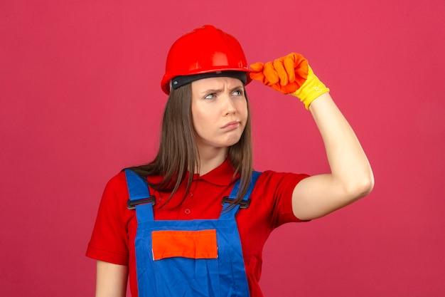 Молодая женщина в перчатках строительной формы и красный защитный шлем, глядя в сторону с сомнительным и скептическим выражением на темно-розовом фоне