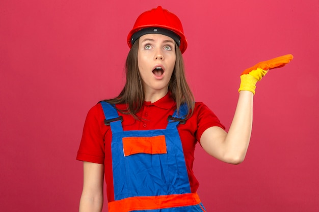 暗いピンクの背景に上げられた手で立っている驚きの表情でショックを受けた建設制服手袋と赤い安全ヘルメットの若い女性