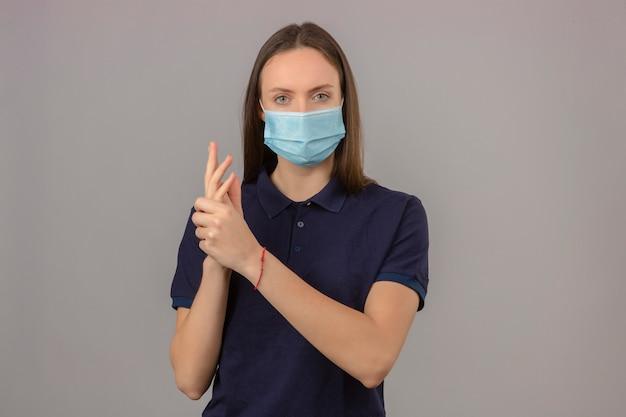 海軍のポロシャツと明るい灰色の背景に立っているカメラを見てきれいな手を示す医療用防護マスクの若い女性
