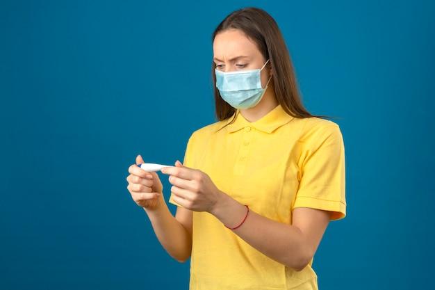 Молодая женщина в желтой рубашке поло и медицинской защитной маске, глядя на термометр с серьезным лицом на изолированных синем фоне