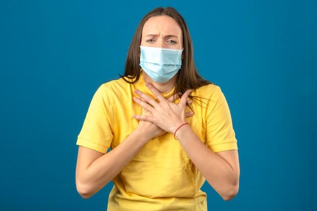 黄色のポロシャツと青い背景に立っている彼女の胸に痛みを持っている病気を探している医療用防護マスクの若い女性