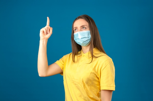 Молодая женщина в желтой рубашке поло и медицинской защитной маске, указывая пальцем на синем фоне