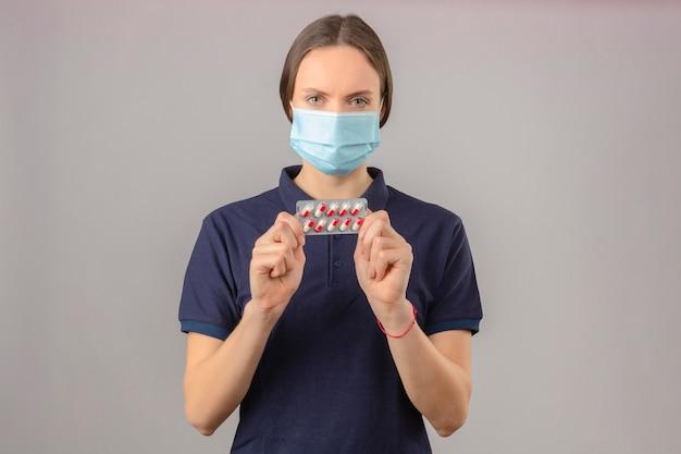 Молодая женщина в синей рубашке поло в защитной медицинской маске, держа в руках блистерные таблетки, смотрит в камеру с серьезным лицом на светло-сером фоне