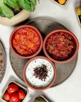 Поднос с разными блюдами и помидорами на столе