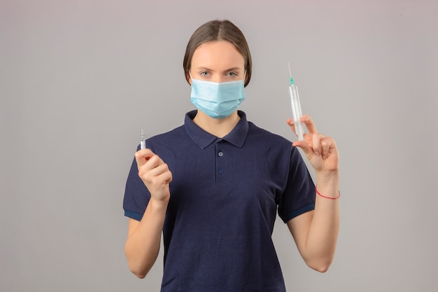 孤立した灰色の背景に深刻な顔立ちでカメラを見て注射器と薬のワクチンの瓶を保持している防護医療マスクで青いポロシャツを着た若い女性