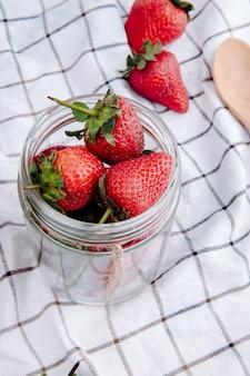 格子縞の生地のガラスの瓶に新鮮な熟したイチゴの側面図