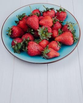 Вид сбоку свежих спелых клубники на синюю тарелку на белом