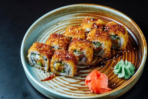 Вид спереди жареные суши с красной рыбой с васаби и имбирем на тарелке