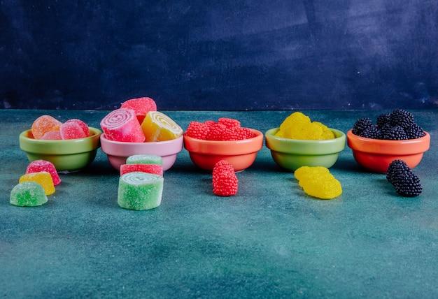 Вид спереди разноцветного мармелада в разноцветных блюдцах для варенья на темно-зеленом
