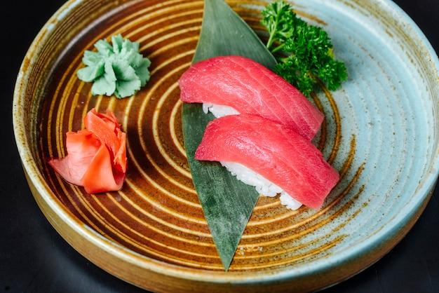 Вид спереди суши с красной рыбой с васаби и имбирем на тарелке