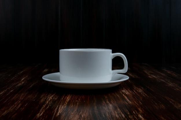 木製の背景の受け皿に正面白いカップ