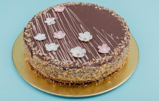 青い表面上のナッツとチョコレートケーキの側面図