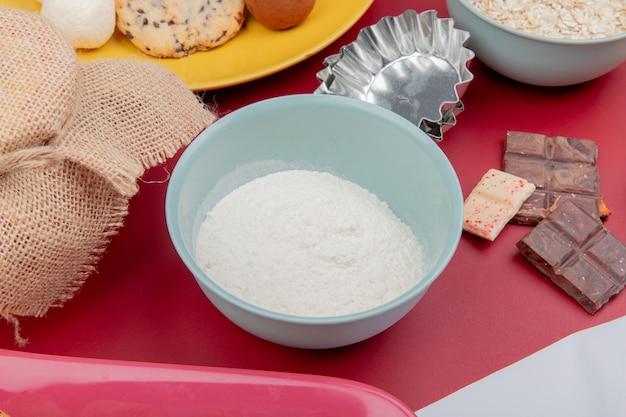 Вид сбоку муки в миску и шоколад с печеньем и овсяными хлопьями на красной поверхности