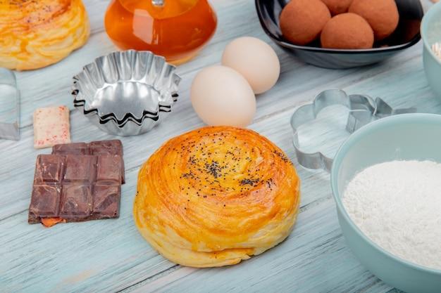 木の表面にチョコレートの卵と小麦粉の甘いバターとゴガルの側面図