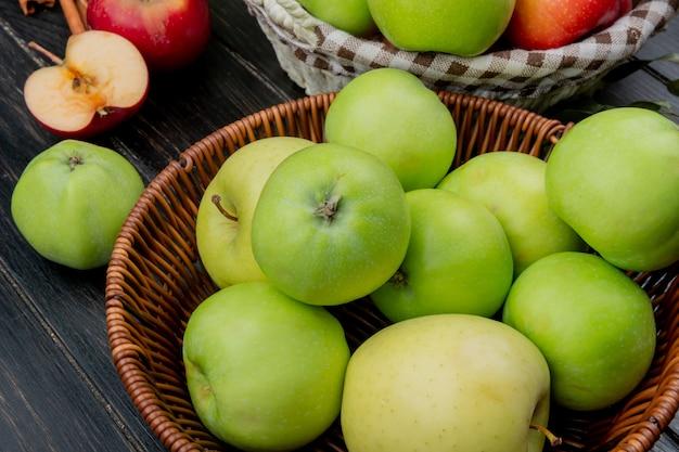 木の表面に全体とカットのリンゴが付いているバスケットの緑のリンゴの側面図