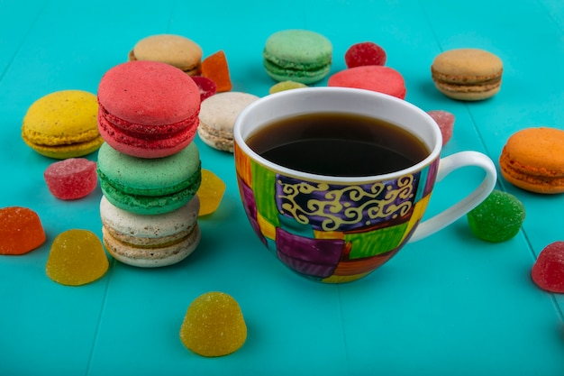 青の背景に一杯のコーヒーとクッキーのサンドイッチの側面図