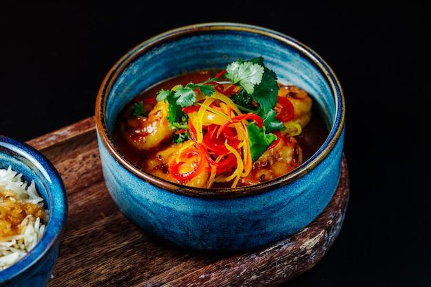 テーブルの上の青いボウルに野菜とサイドビューシーフードスープ