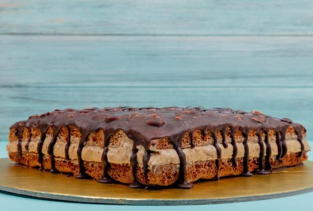 コピースペースを持つ青い表面にスニッカーズケーキの側面図