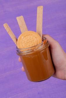 紫色の表面にクッキーとピーナッツバターの瓶を持っている手の側面図