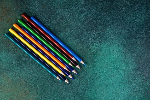 緑の背景に平面図コピースペースカラフルな鉛筆