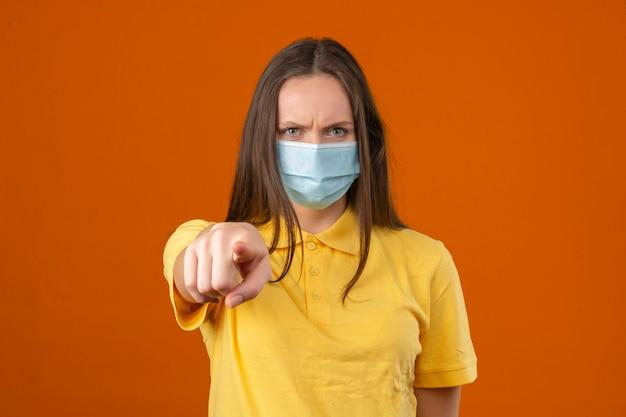 オレンジ色の背景に立っている怒っている顔をしてカメラに保護医療マスク人差し指で黄色のポロシャツを着た若い女性