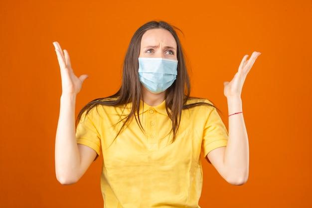 黄色のポロシャツと孤立したオレンジ色の背景にパニックに肩をすくめて医療用防護マスクの若いショックを受けた女性