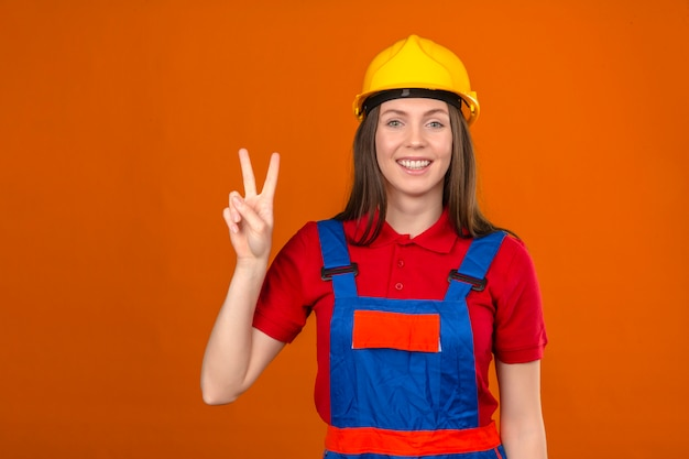 Молодая женщина в строительной форме и желтый защитный шлем, показывая знак победы номер два, улыбаясь стоя на оранжевом фоне