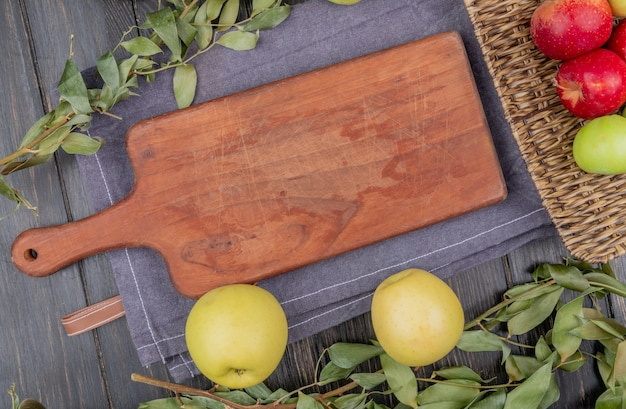 木製の背景の葉と灰色の布のまな板の周りのリンゴのトップビュー