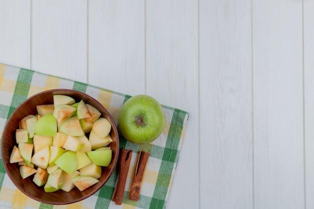 Вид сверху яблочных кубиков в миску и весь с корицей на клетчатой ткани и деревянный фон с копией пространства