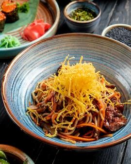 Вид сбоку жареной лапши с говядиной и овощами в тарелке на деревянный стол