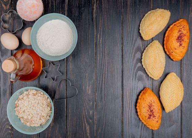 コピースペースを持つ木製の背景に小麦粉オート麦フレークバターシャカルブラとしてベーカリー製品のトップビュー
