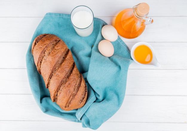 木製のテーブルに溶かしバターと青い布に黒いパンと牛乳の卵のトップビュー