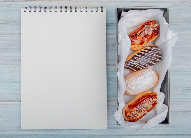 コピースペースを持つ木製の背景のケーキとメモ帳のトップビュー