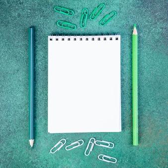 トップビューコピースペースライトグリーンとブルーの鉛筆、ペーパークリップ、緑の背景にメモ帳