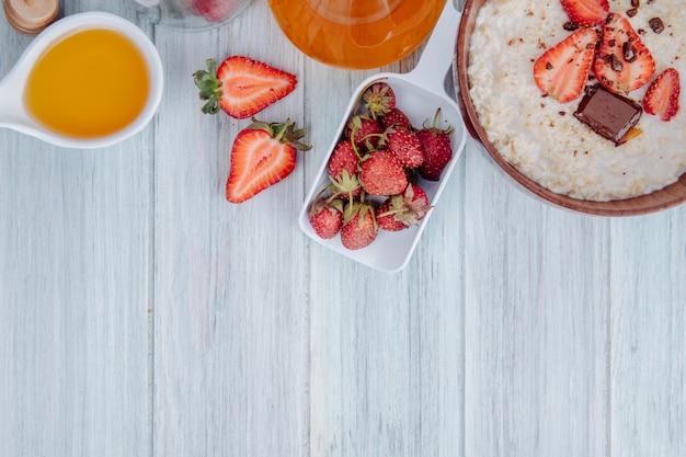 コピースペースを持つ白い木の新鮮な熟したイチゴと蜂蜜の木製ボウルにオートミールのお粥の平面図