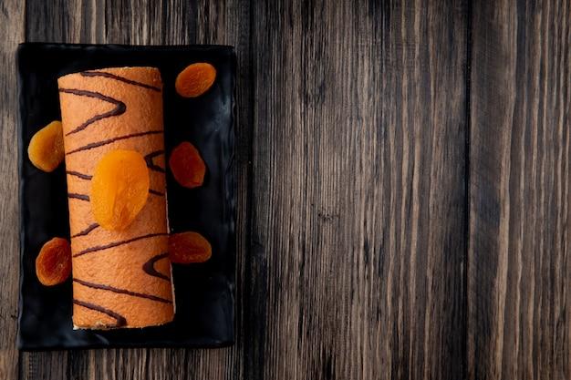 コピースペースを持つ素朴な木の上の黒いトレイにドライアプリコットで飾られたロールケーキのトップビュー