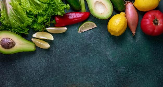 濃い緑色の背景に野菜アボカドレモン赤唐辛子玉ねぎとレタスの平面図コピースペースミックス