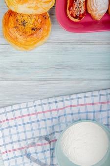 布とコピースペースを持つ木製の背景にケーキと小麦粉とゴゴールのトップビュー