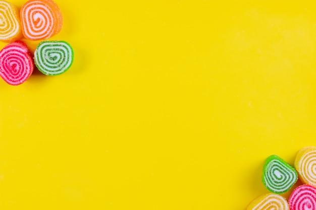 トップビューコピースペース黄色の背景にマルチカラーのマーマレード