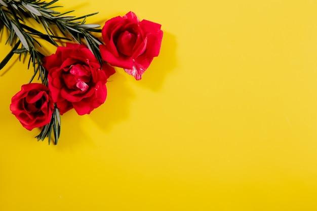 黄色の背景にピンクのバラでトップビューコピースペースローズマリーの枝