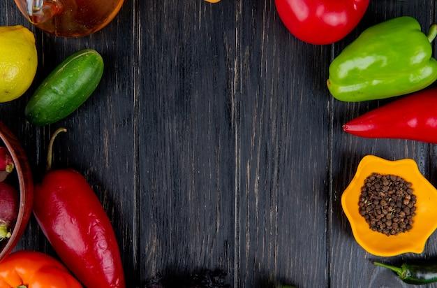 コピースペースを持つ暗い木の新鮮な野菜のカラフルなピーマン緑唐辛子キュウリトマトと黒胡椒で作られたフレームのトップビュー