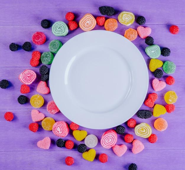 Вид сверху копия пространства белая тарелка с разноцветным мармеладом вокруг на светло-фиолетовом фоне