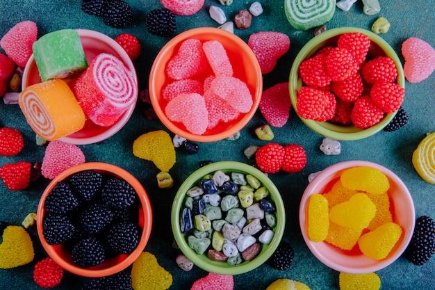 Вид сверху разноцветного мармелада в разных формах в блюдца для варенья на темно-зеленом фоне
