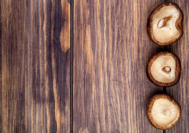 コピースペースを持つ素朴な木材に分離された行に並ぶ新鮮なキノコのトップビュー