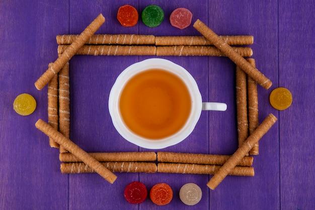 Вид сверху хрустящие палочки и мармелад с чашкой чая в центре на фиолетовом фоне